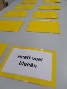 Tafel met omgedraaide kaartjes. Een complimenten kaartje is wel gedraaid en daar staat  op: 'Heeft veel ideeën'.